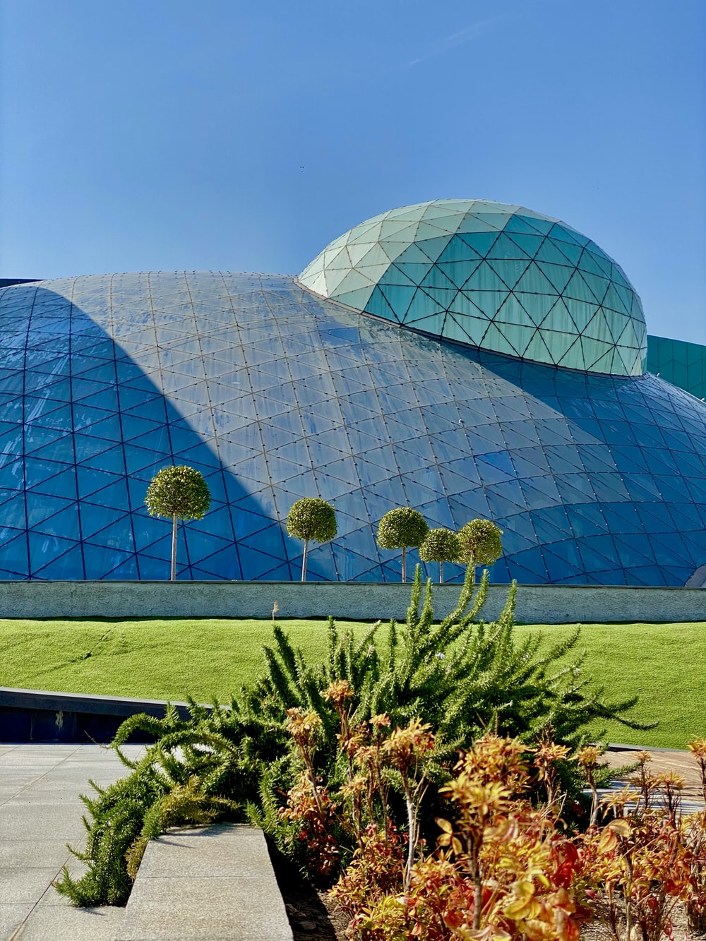 blue glass dome building near green grass field during daytime