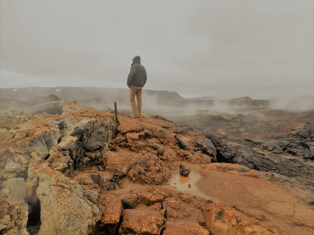 man in black jacket standing on brown rock formation during daytime