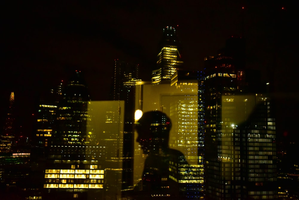 silhouette of man standing near high rise building during night time