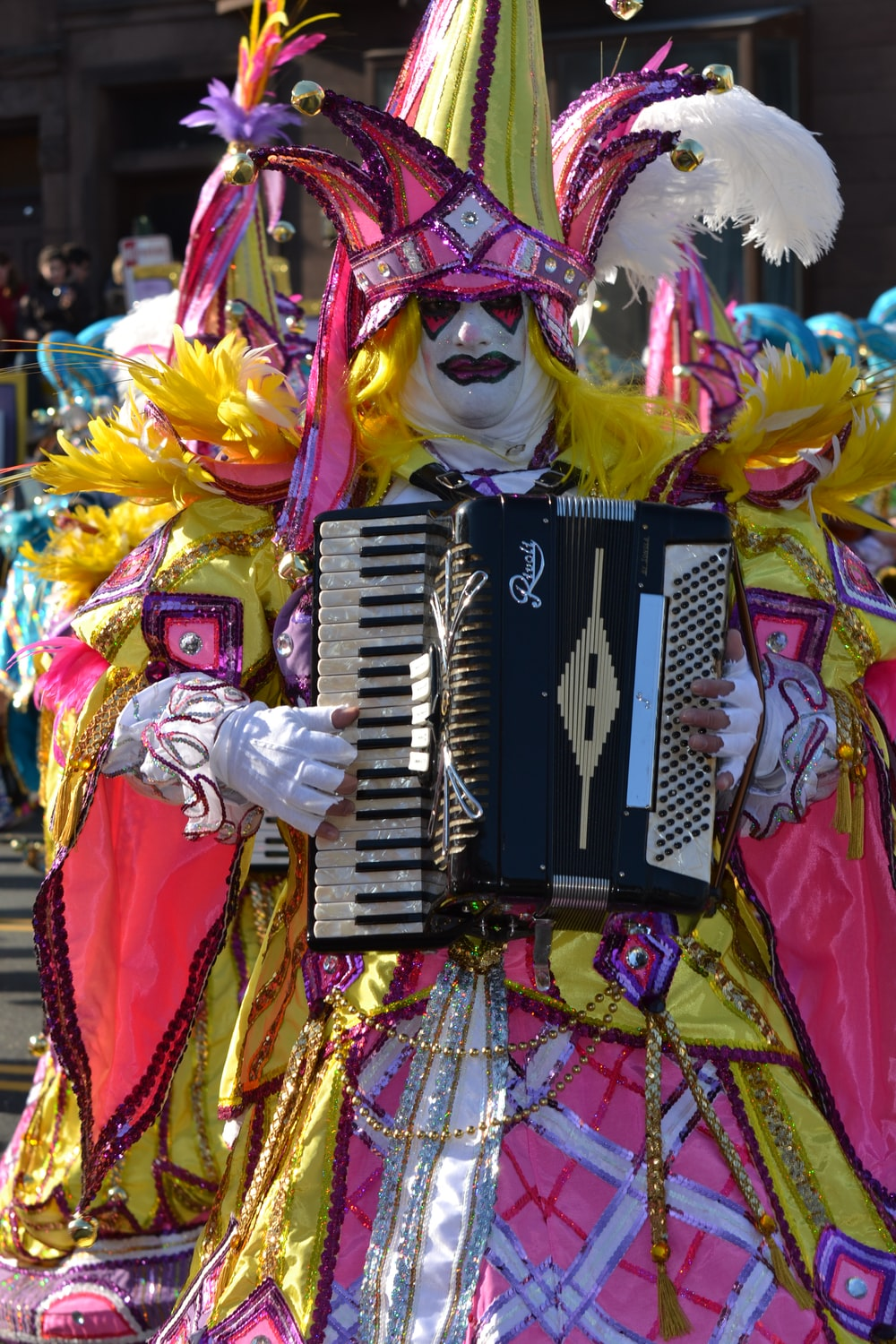 person in yellow and red costume playing black and white electric keyboard