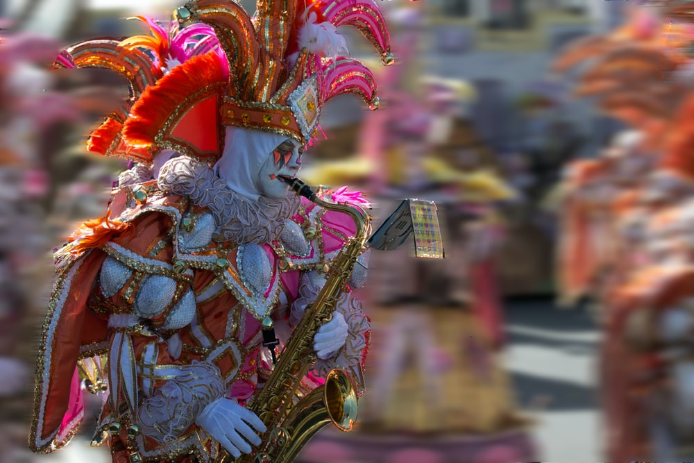 people in gold and red dragon costume walking on street during daytime