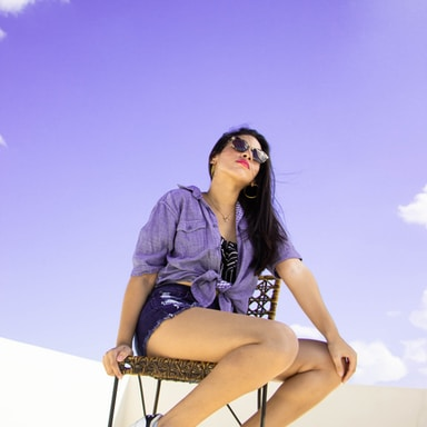 woman in black and white dress wearing sunglasses sitting on white chair