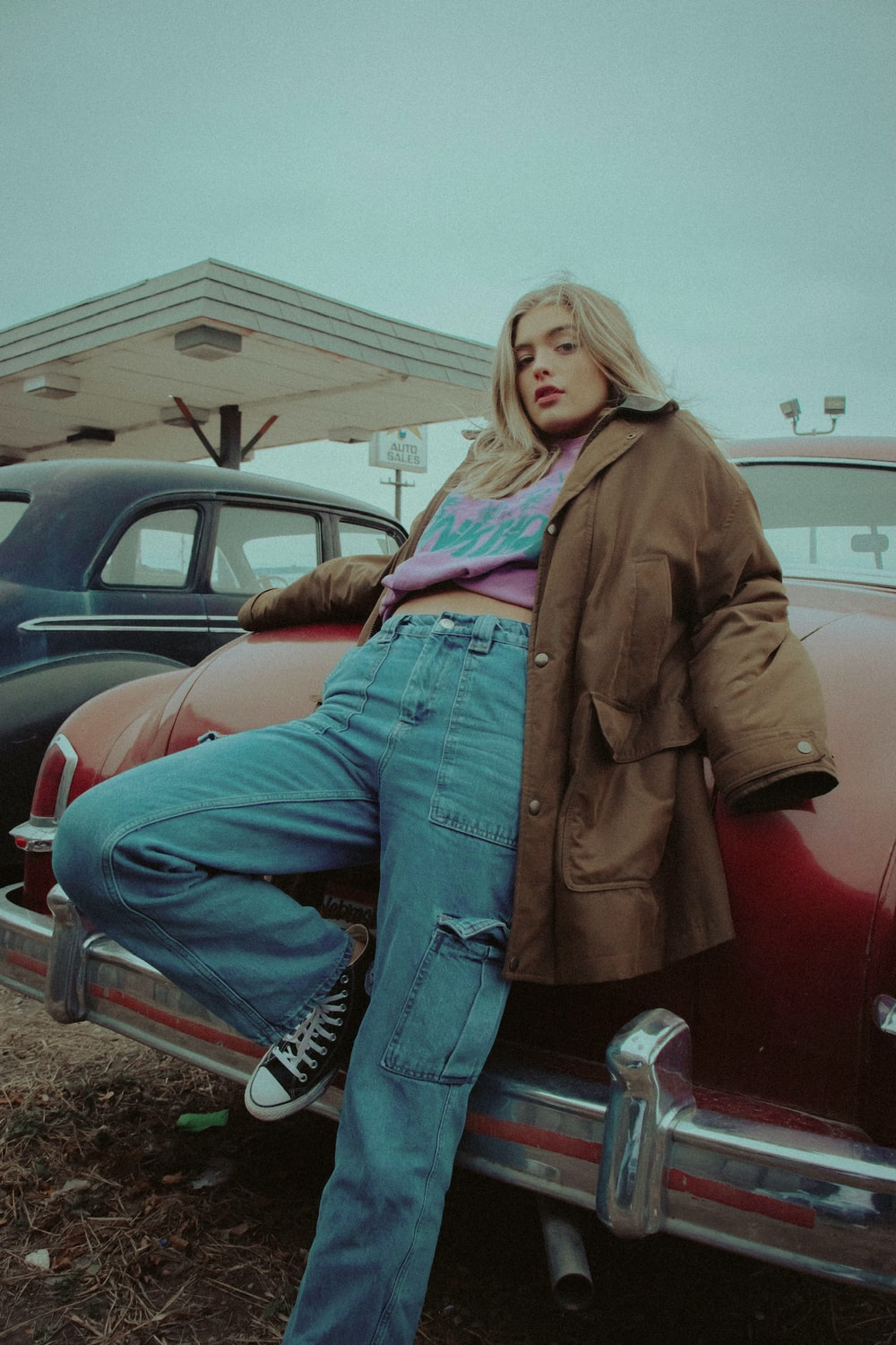 woman in brown jacket and blue denim jeans sitting on red car