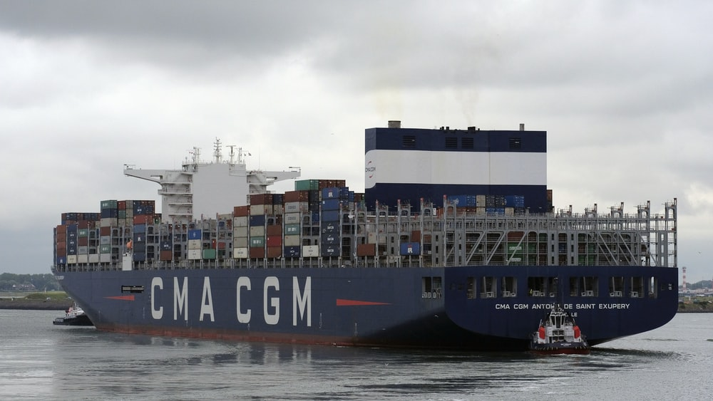 black cargo ship on sea under white sky during daytime