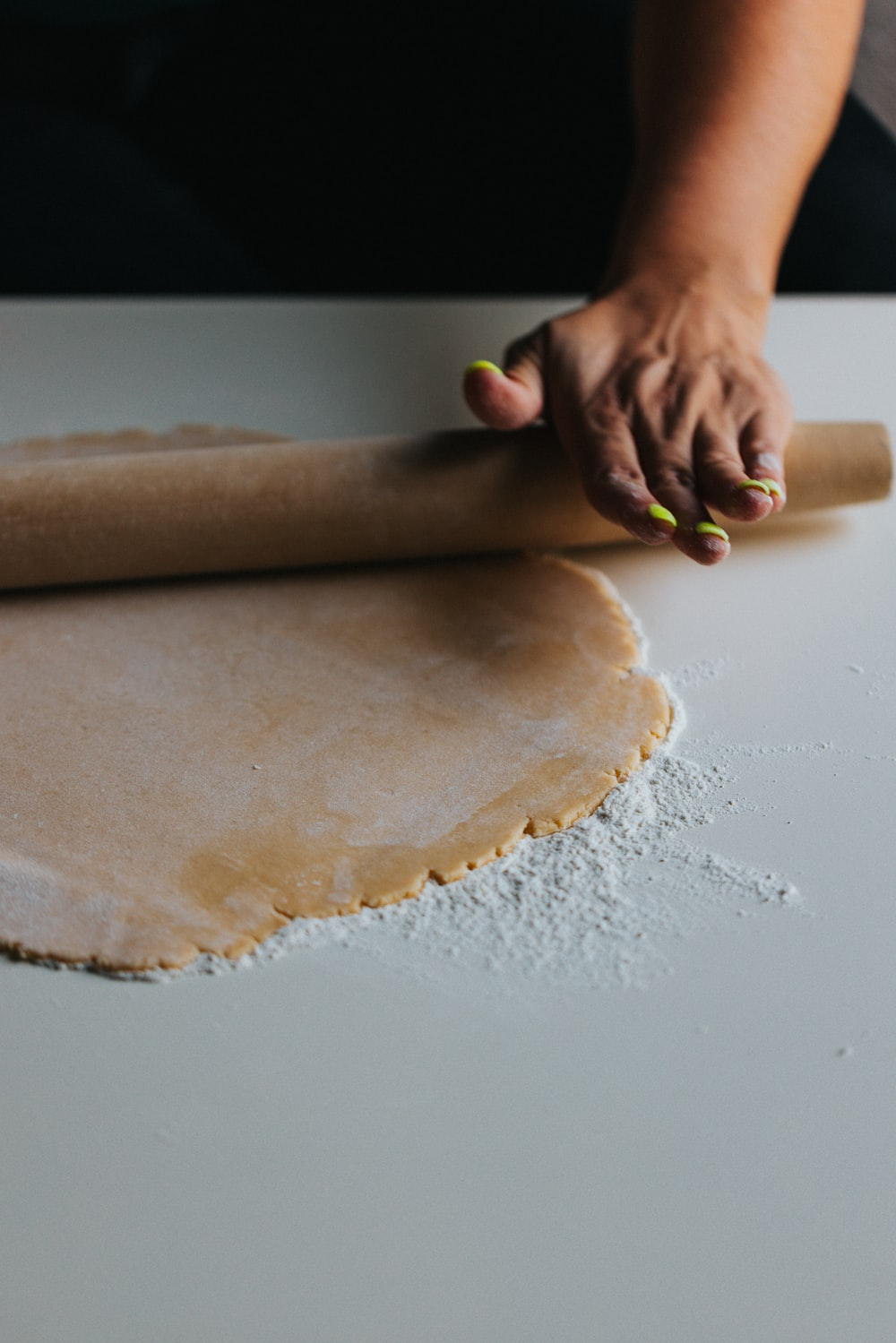 person holding brown dough on white table