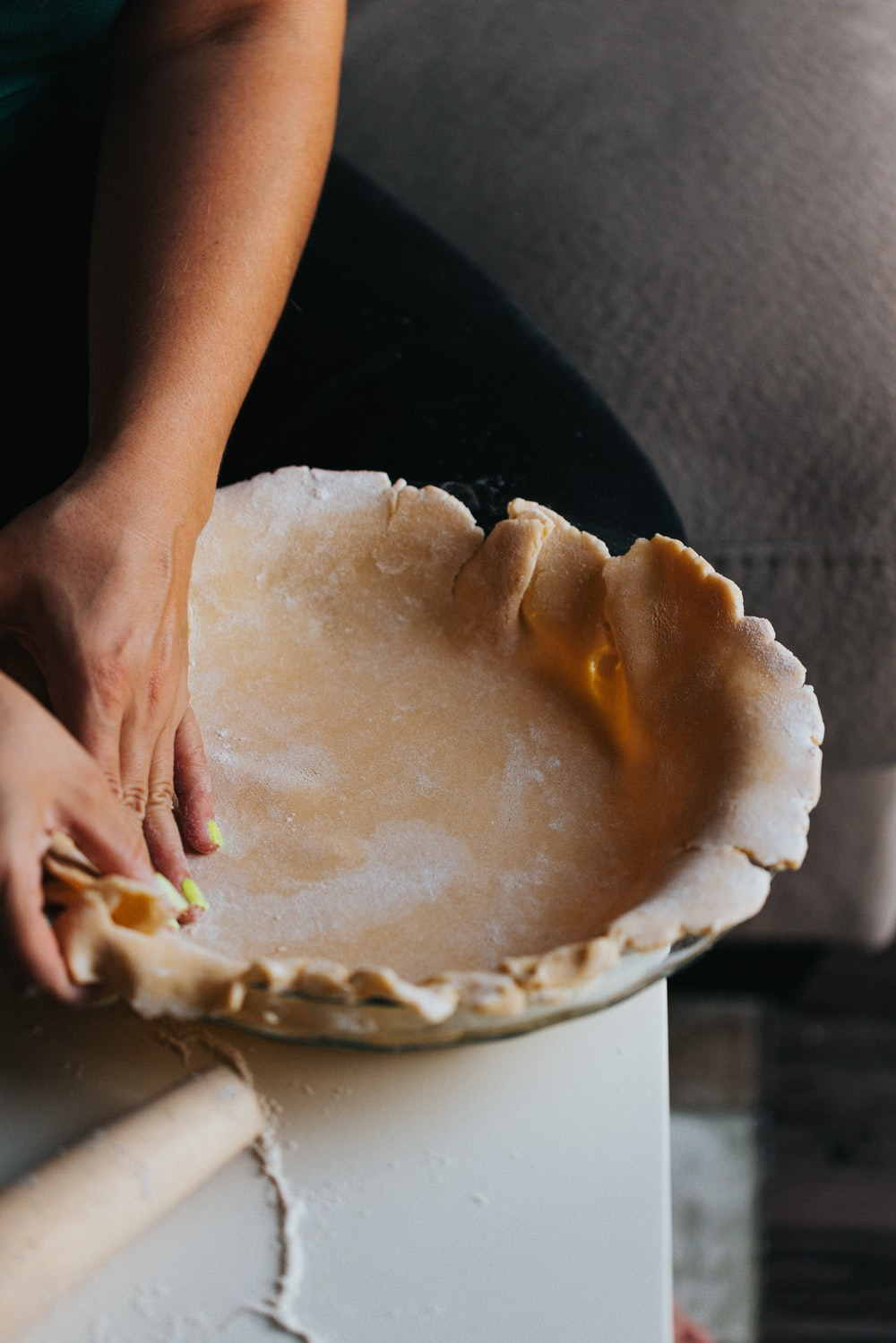 person holding white ceramic bowl with brown and white cake