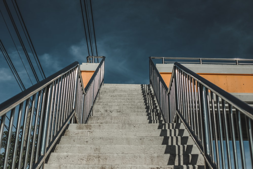 gray concrete staircase with orange railings