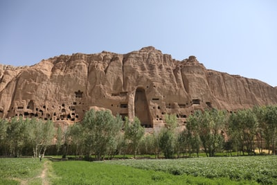 brown rock formation near green trees during daytime afghanistan zoom background