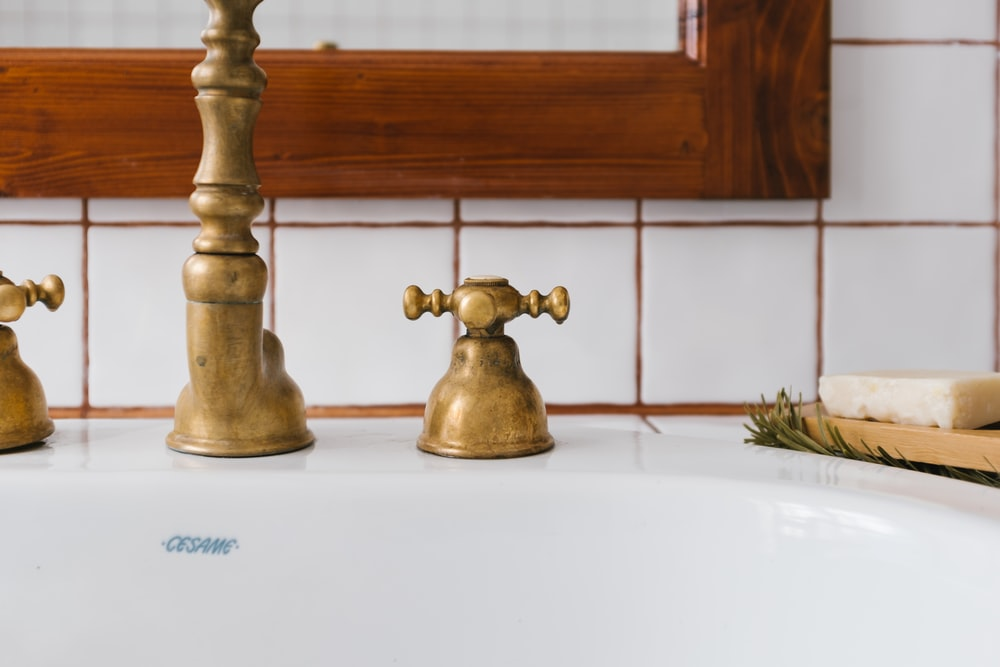 brass faucet on white ceramic sink