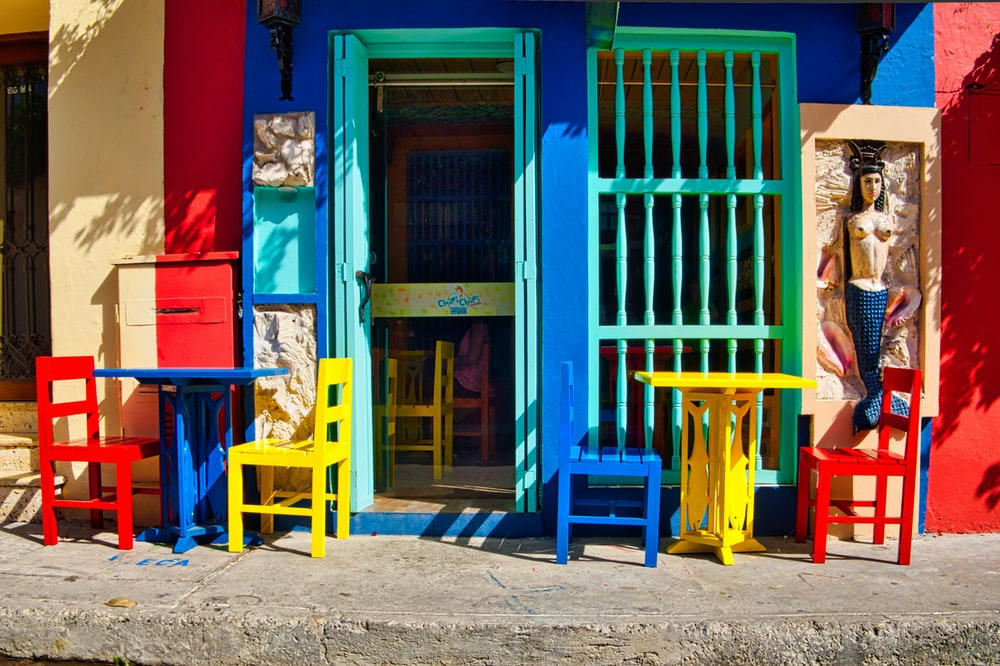 blue wooden door with red and blue wooden chairs