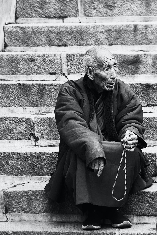 man in black coat standing beside brick wall