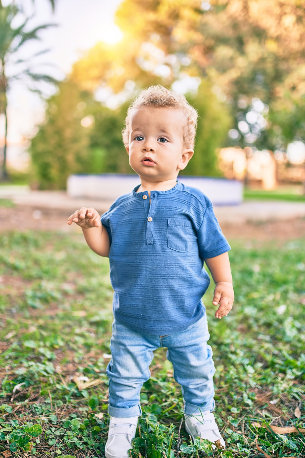 boy in blue polo shirt and blue denim shorts standing on green grass field during daytime