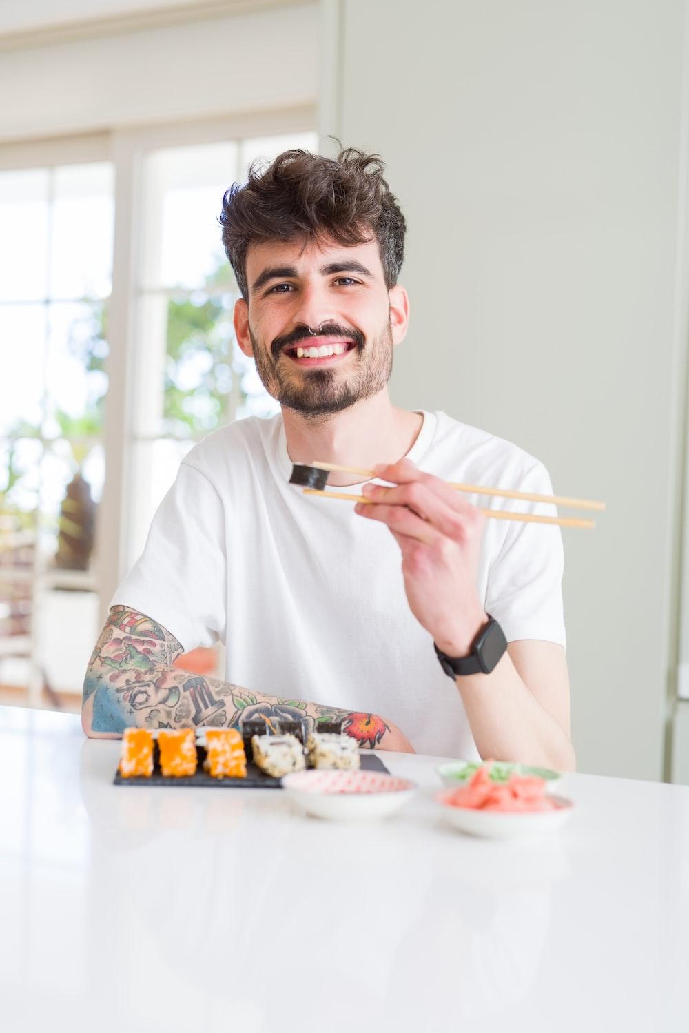 man in white crew neck t-shirt holding white chopsticks