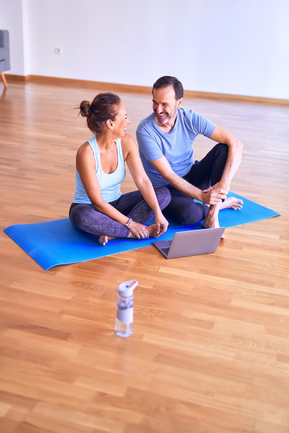 man in white tank top and gray pants sitting on blue yoga mat
