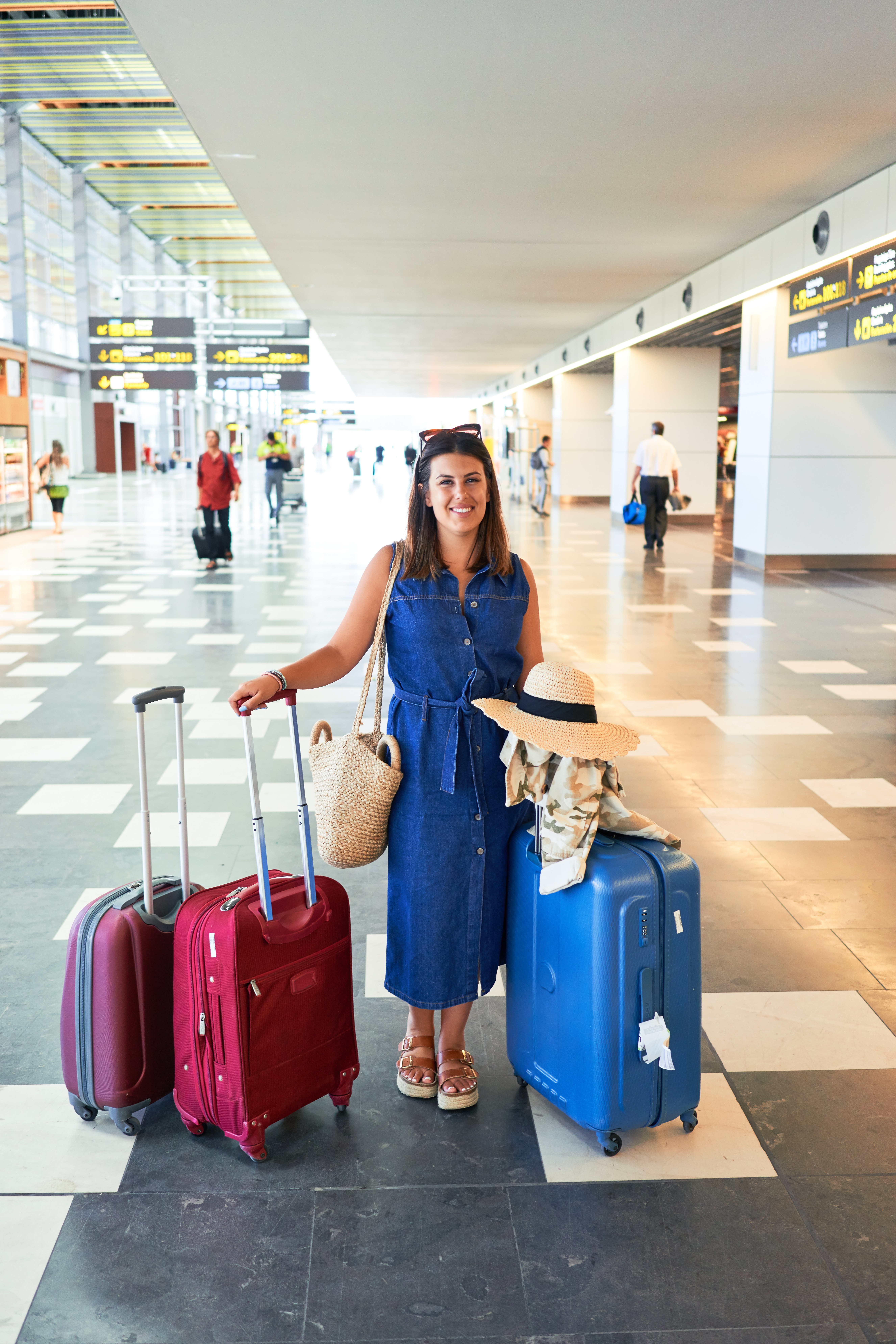 Young beautiful woman at the airport standing with suitcases ready for a vacation trip