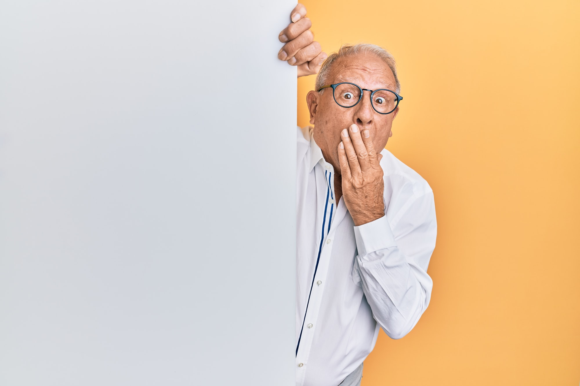 Senior caucasian man holding blank empty banner covering mouth with hand, shocked and afraid for mistake. surprised expression