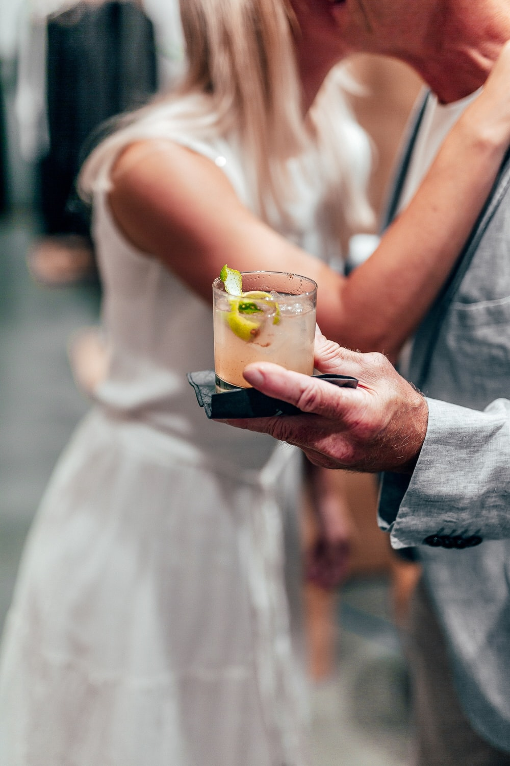 woman in white dress holding drinking glass with yellow liquid
