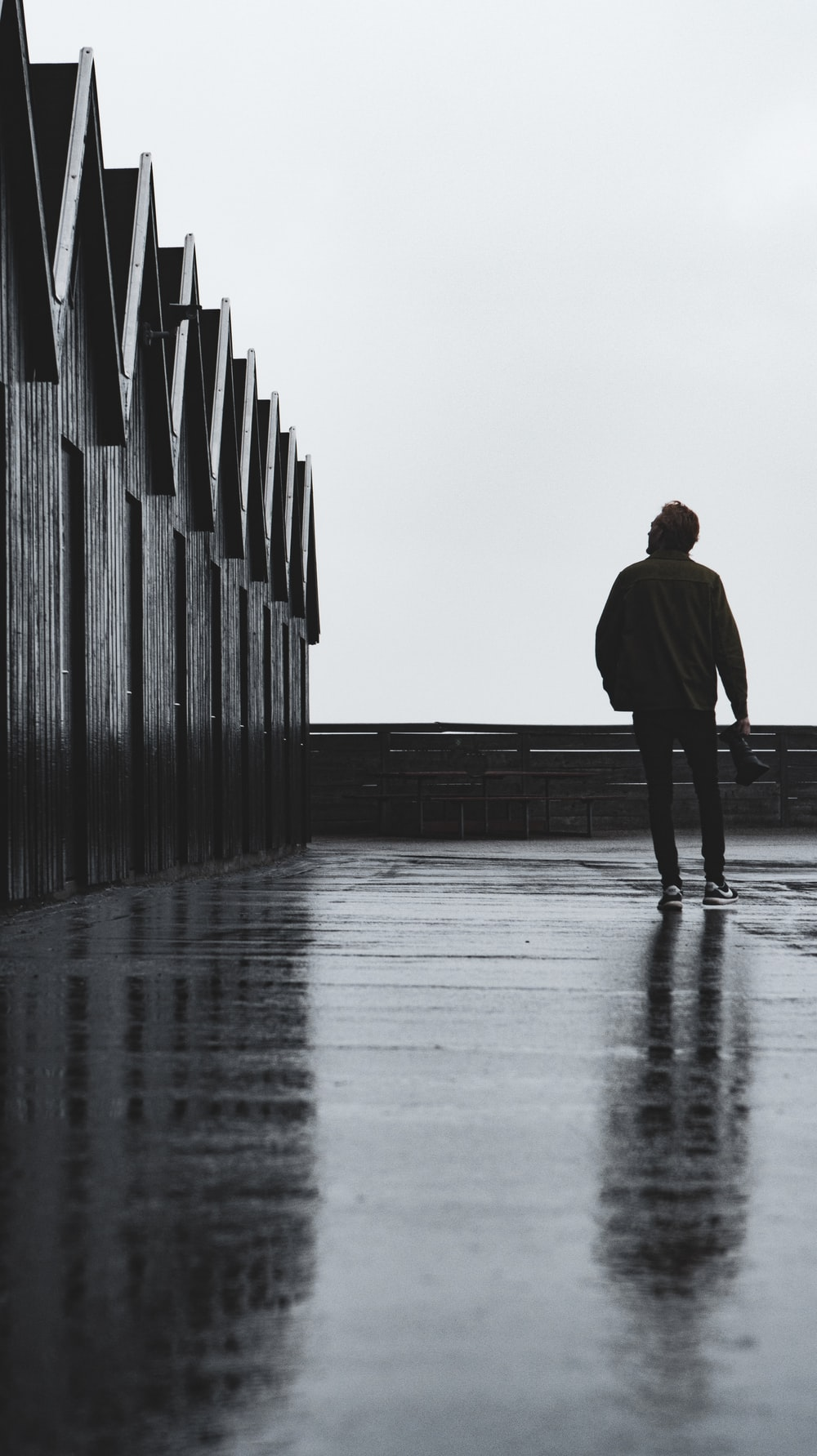 man in black coat walking on gray concrete stairs