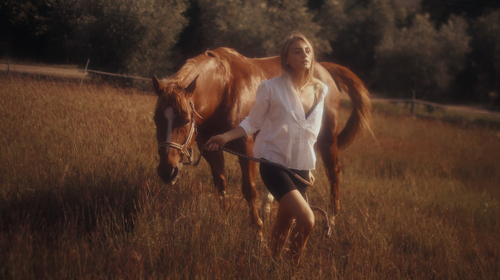 woman in white long sleeve shirt and black shorts standing beside brown horse during daytime