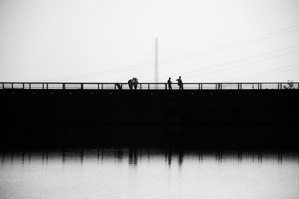 silhouette of people standing on dock in grayscale photography