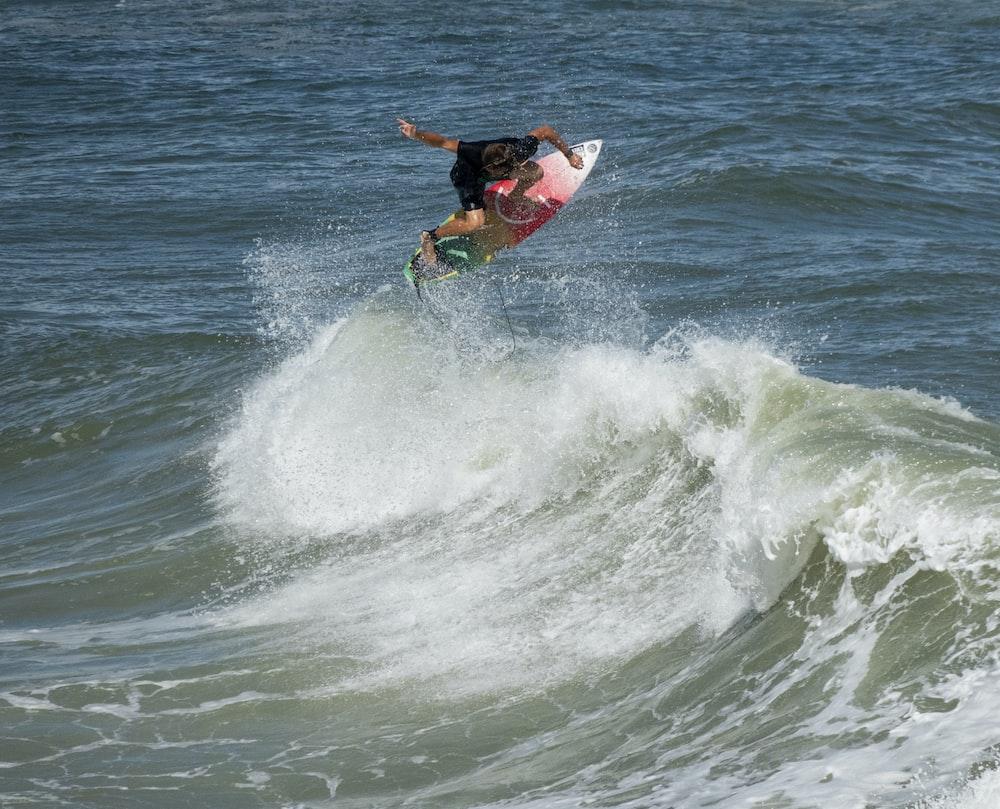 man in black shirt surfing on sea waves during daytime