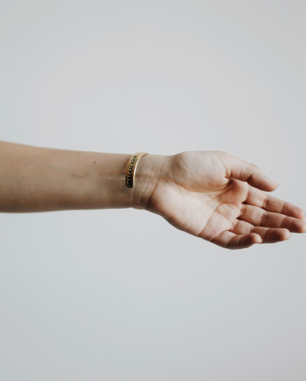 person wearing gold bracelet and gold bracelet