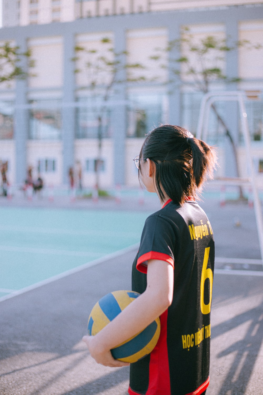 woman in black and yellow jersey shirt standing on track field during daytime