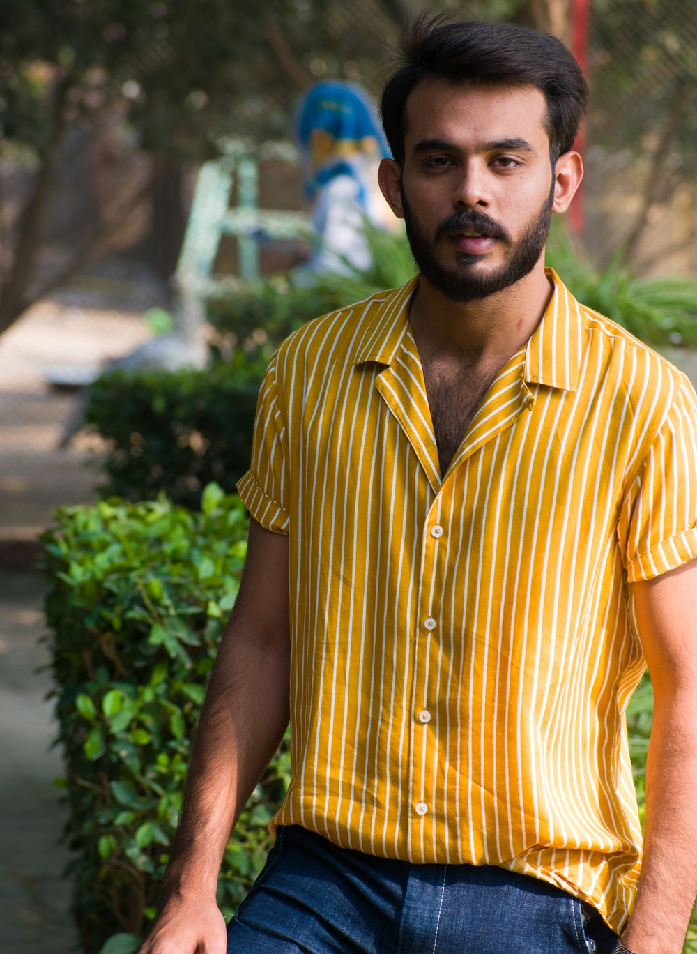 man in yellow and white striped button up shirt standing near green plants during daytime