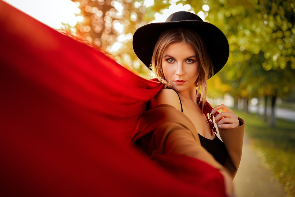 woman in red long sleeve shirt wearing black hat