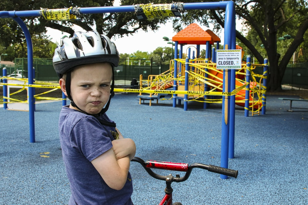 boy in blue denim vest and helmet riding red bicycle