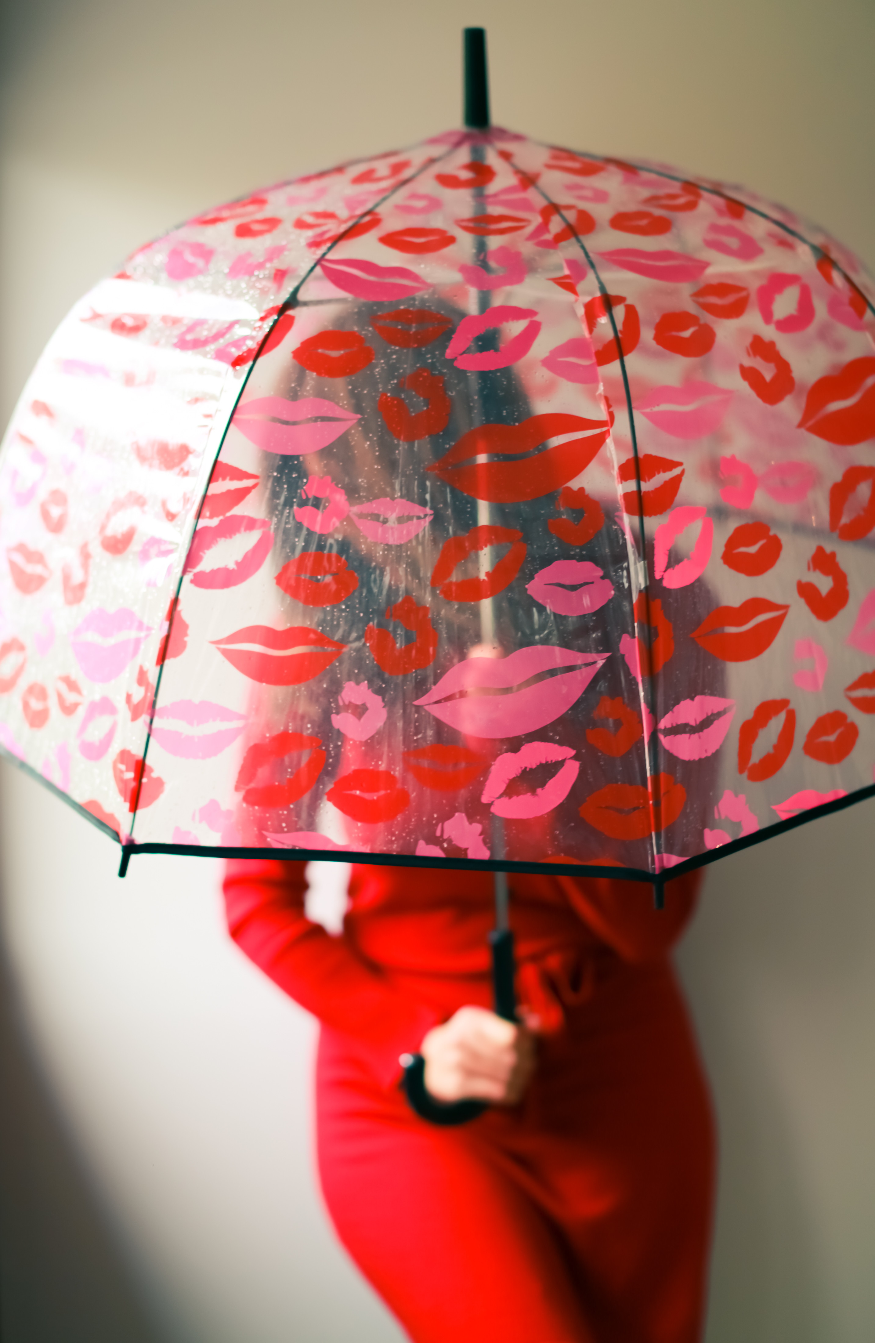 person in red long sleeve shirt holding white and red umbrella