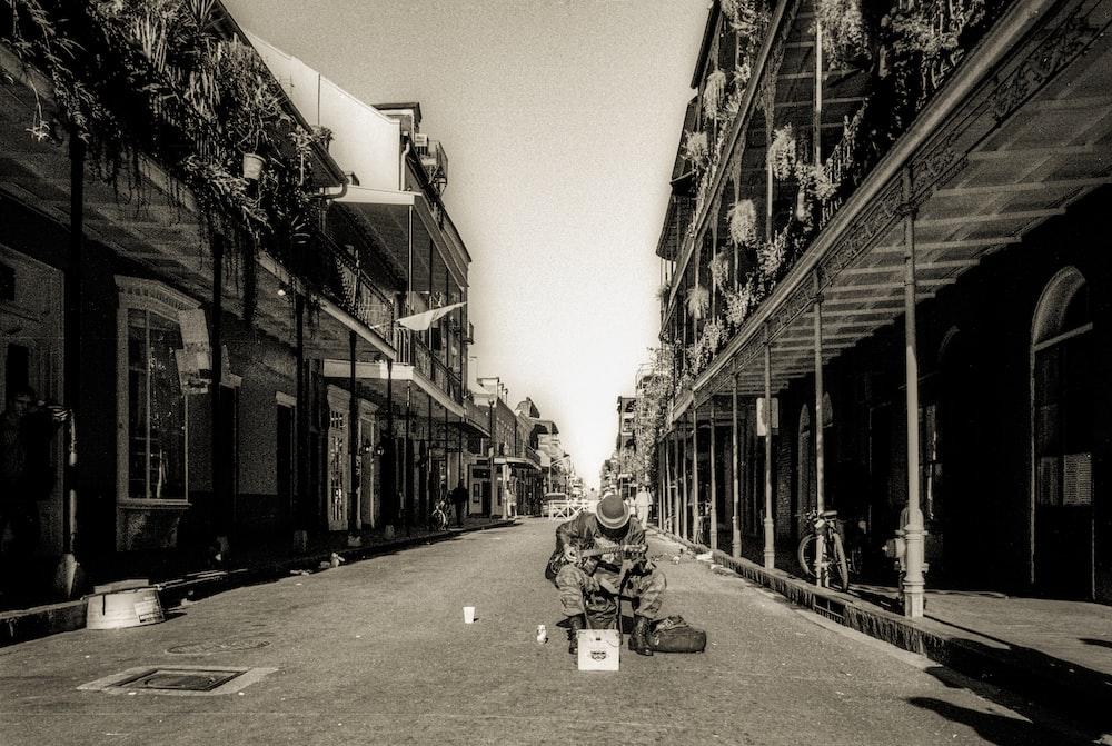 grayscale photo of people walking on street in between buildings