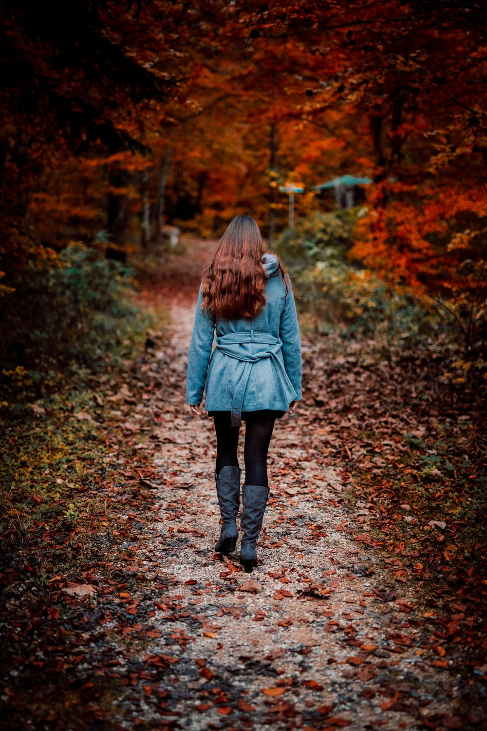 woman in gray coat walking on brown dried leaves on pathway