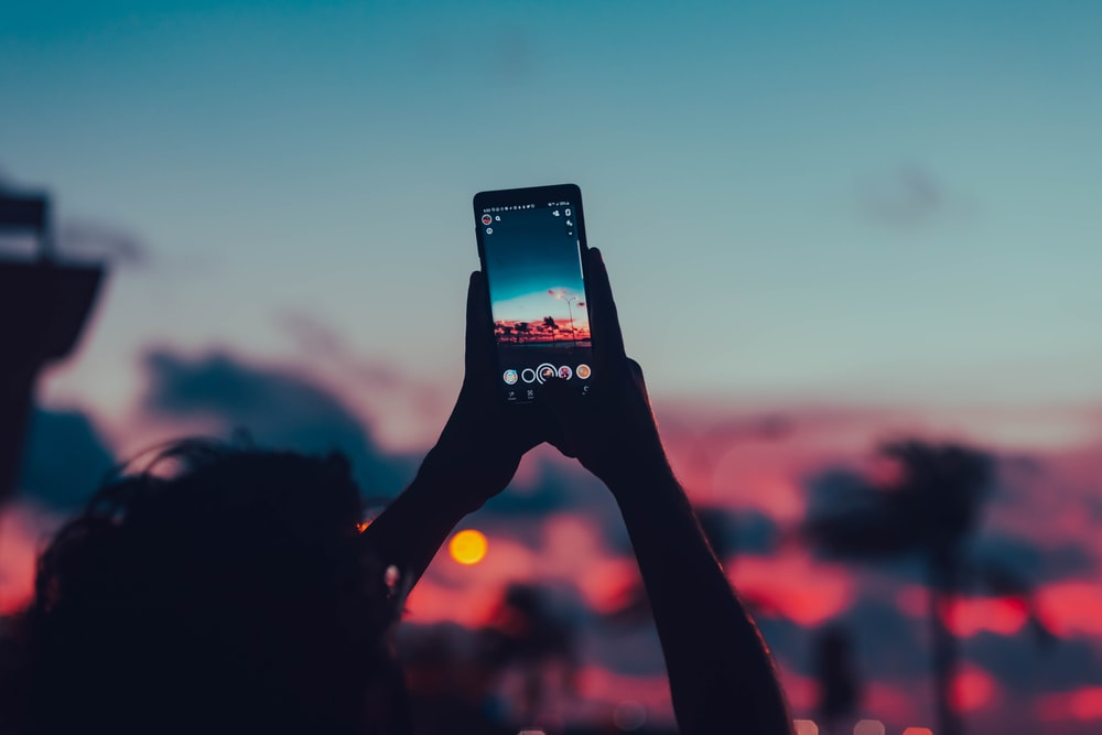 person holding black smartphone taking photo of sunset