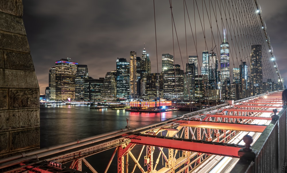 red metal bridge over river during night time