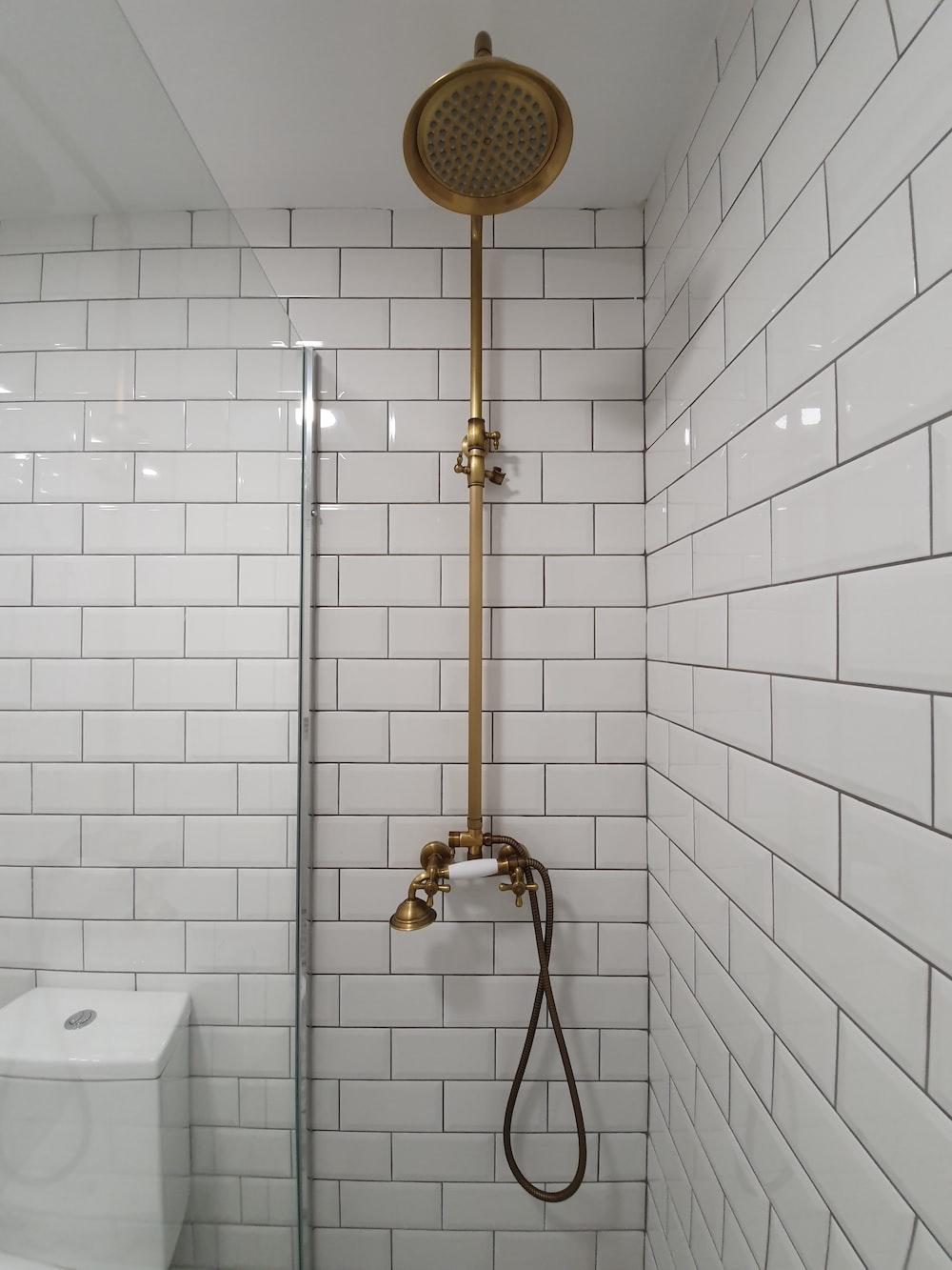 gold shower head on white ceramic bathtub