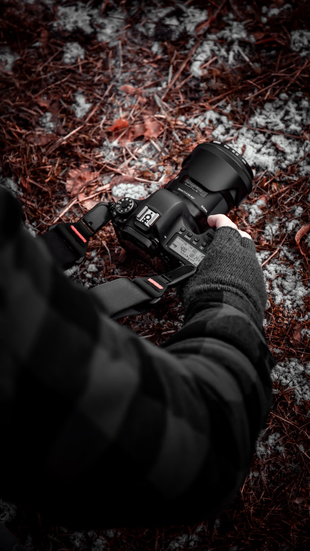 person in black and red jacket holding black dslr camera
