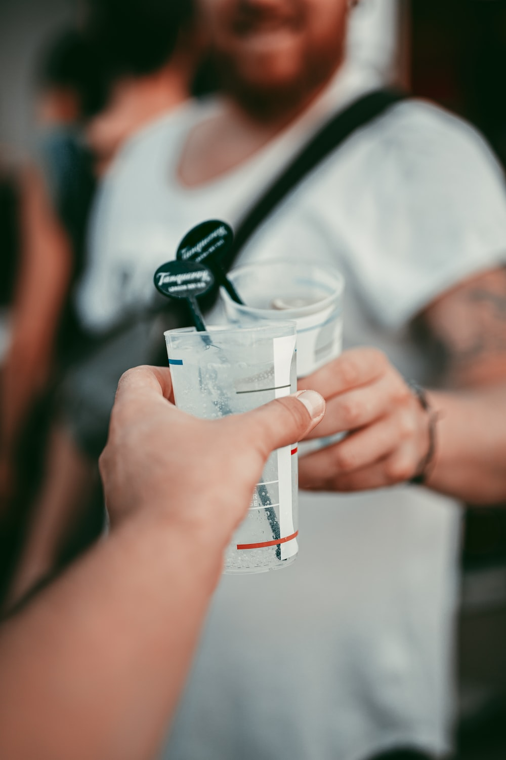 person holding clear plastic cup with black plastic straw