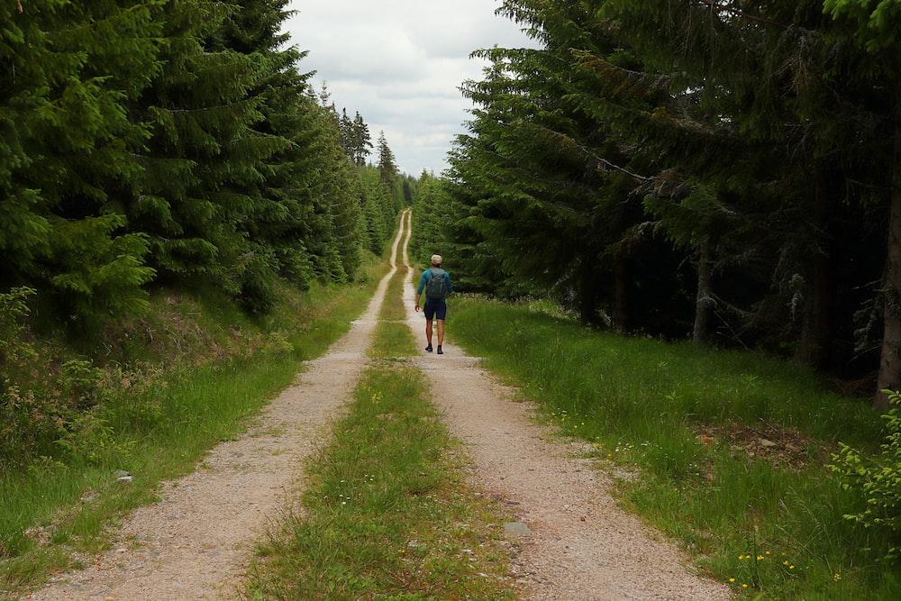 man in blue shirt walking on dirt road