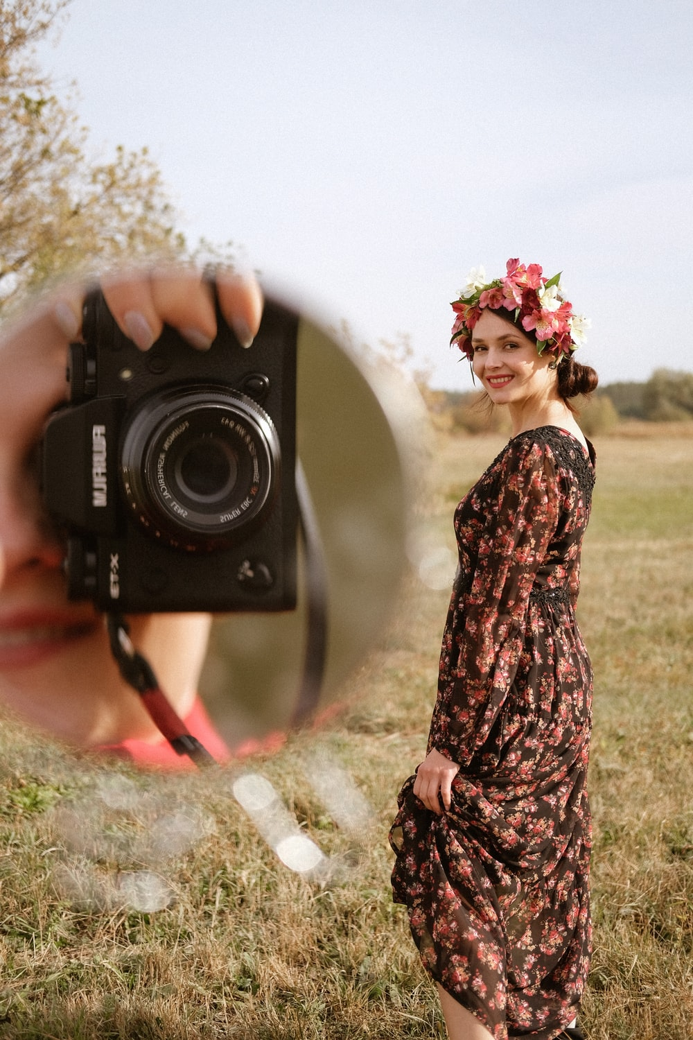 woman in black and brown floral dress holding black nikon dslr camera