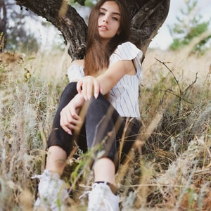 woman in white shirt and black skirt sitting on tree trunk
