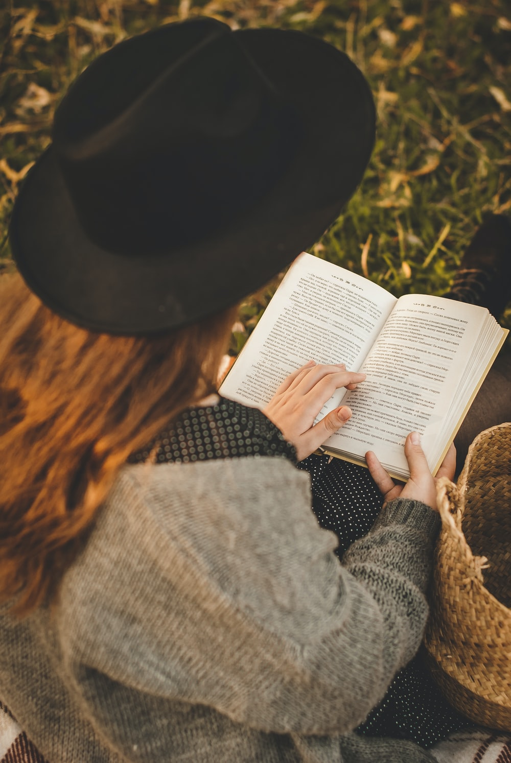 woman in gray sweater and black hat reading book