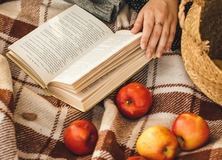 person holding book page with red apple fruits on brown woven basket