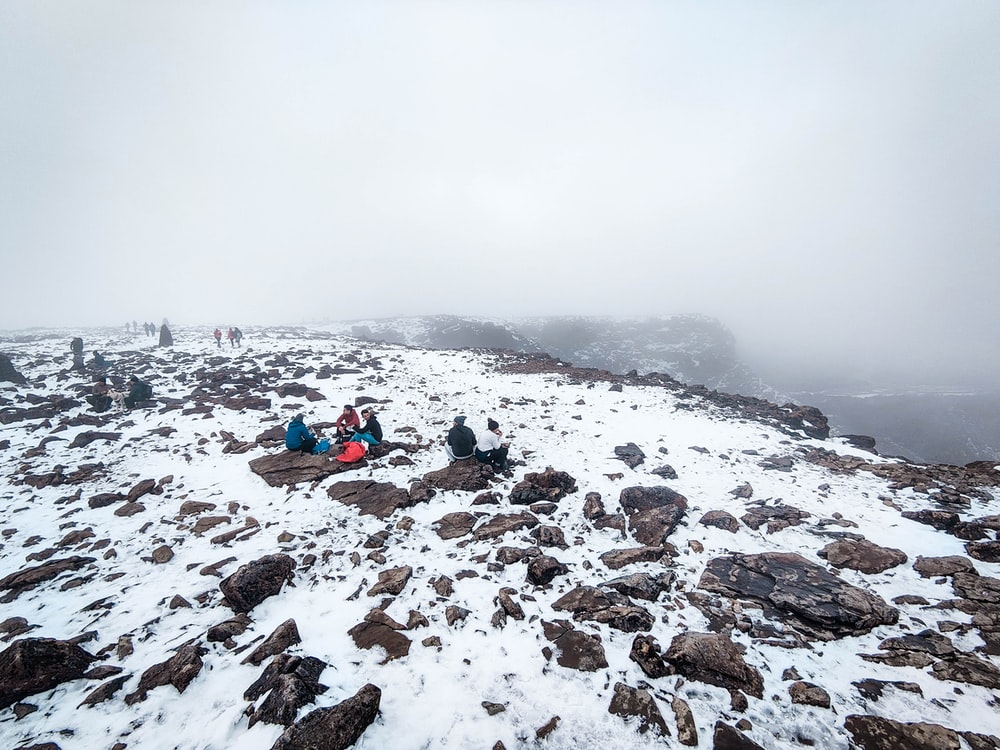 people sitting on snow covered ground during daytime