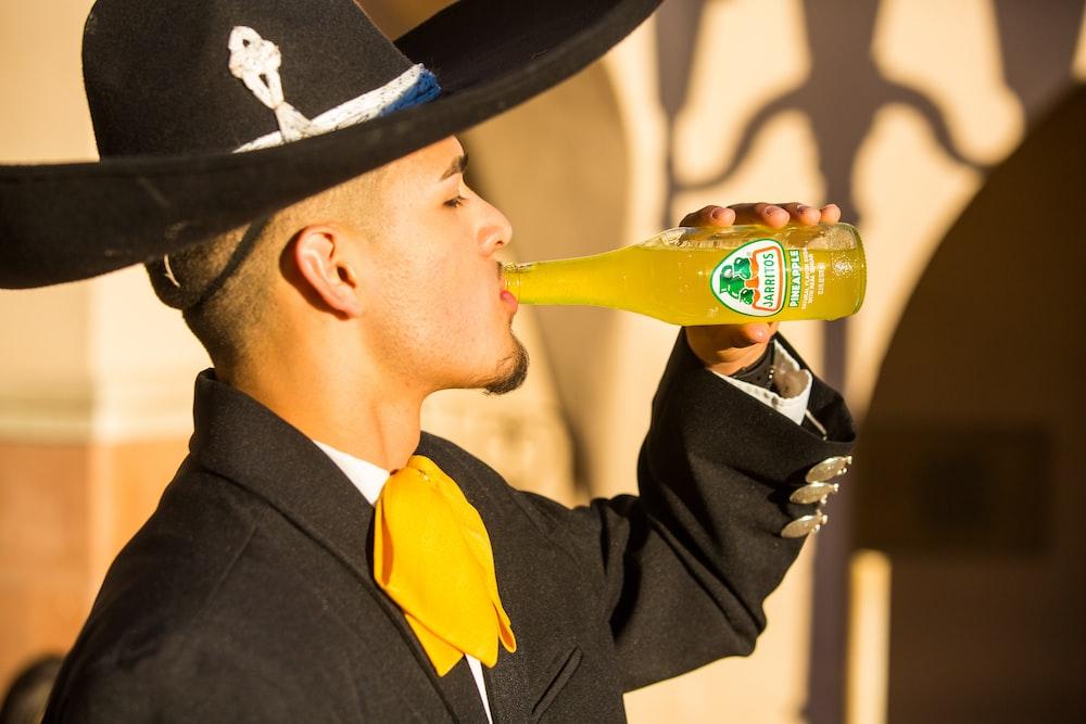 man in black hat drinking beer