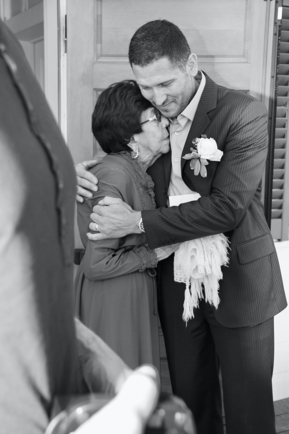 man in suit kissing woman in wedding dress in grayscale photography