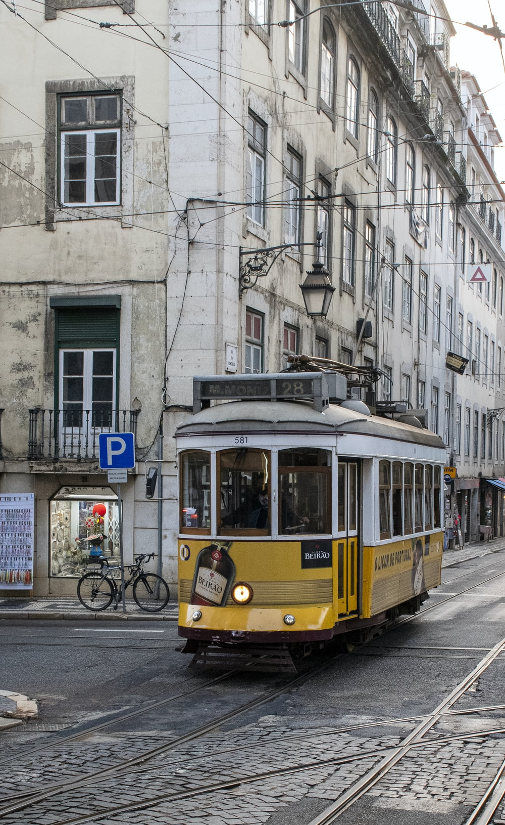 yellow tram on road near building during daytime