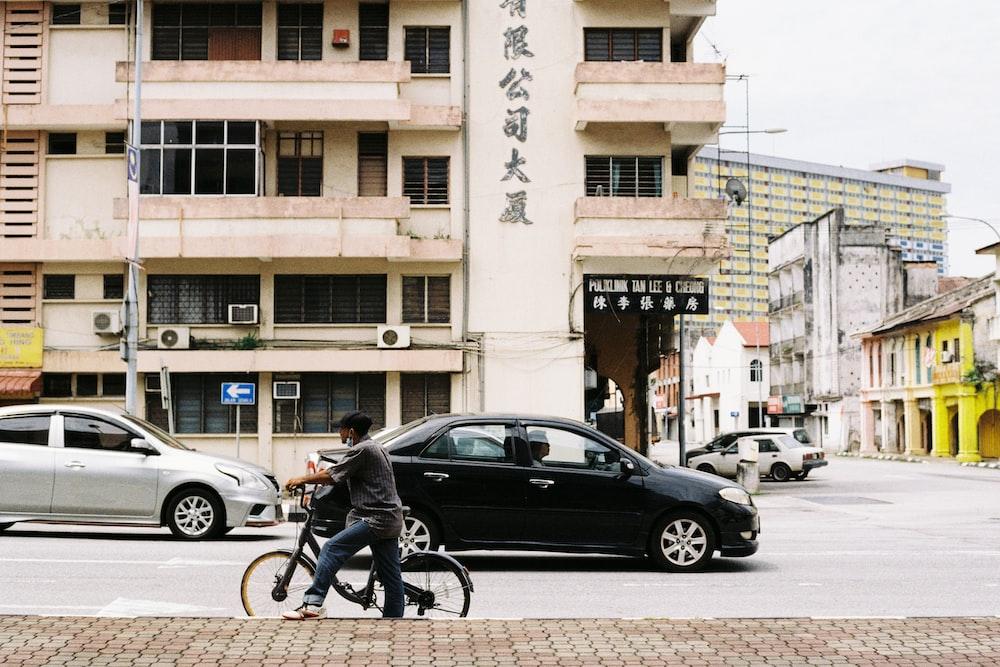 man in black jacket riding bicycle near black sedan during daytime