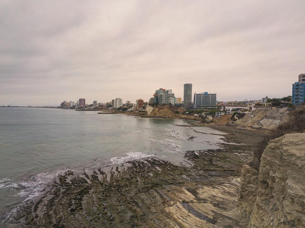 city skyline near sea under cloudy sky during daytime
