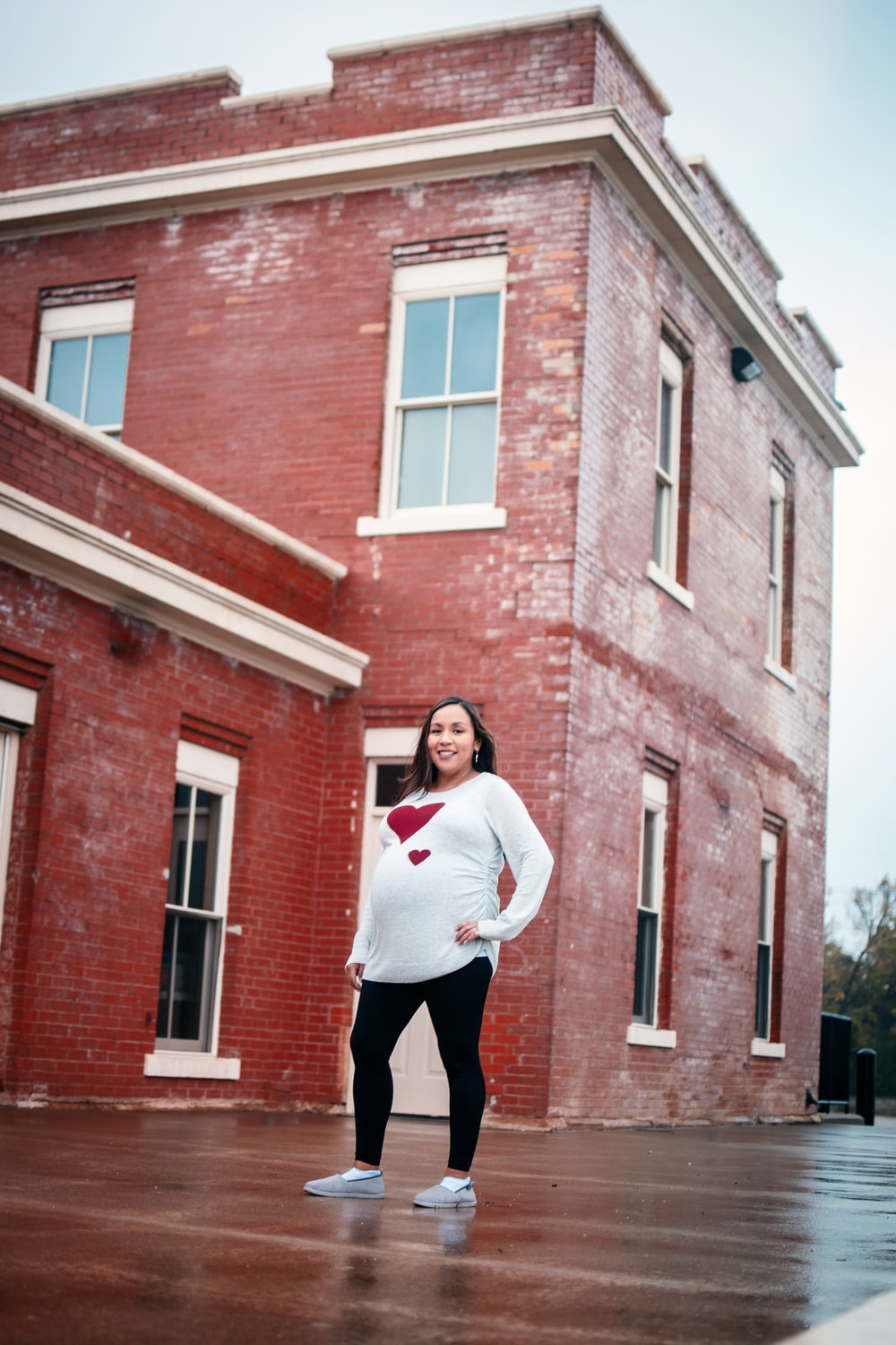 woman in white long sleeve shirt and black pants standing in front of brown brick building
